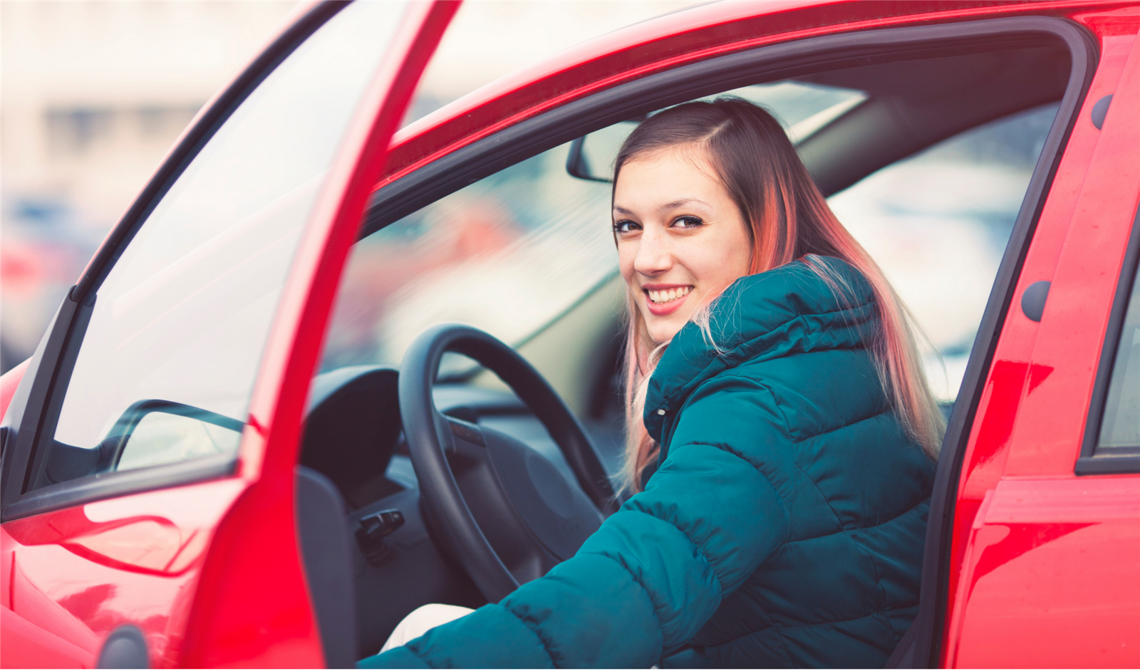 Girl smiling from inside red car with door open