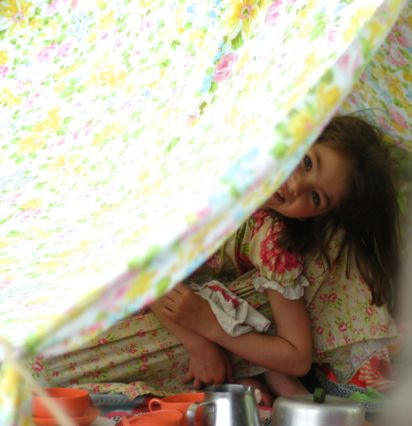 Child with an outdoor blanket fort