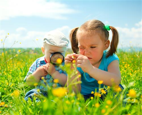Children exploring nature with magnifying glass