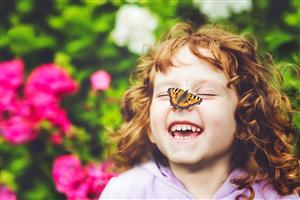Laughing girl with butterfly on nose