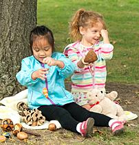 Children playing outside with pinecones