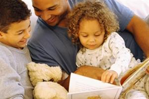 Father reading bedtime stories to children