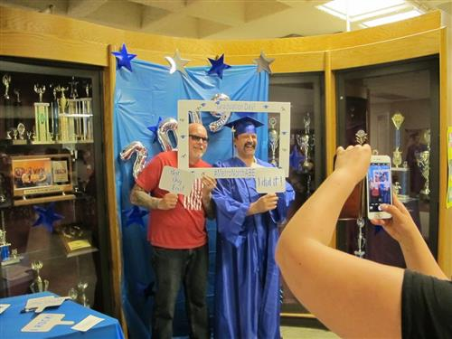 Students pose for photo booth at recent adult graduation ceremony