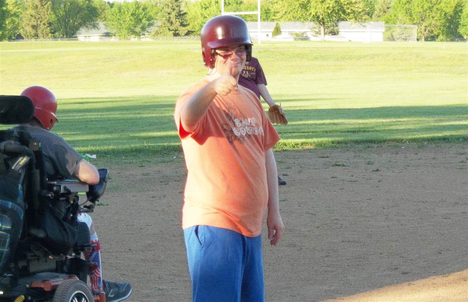 adults with disabilities play on softball field