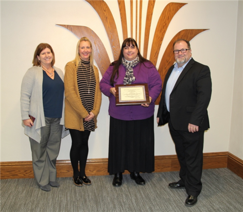 Adult learning team accepts international programming award at school board meeting