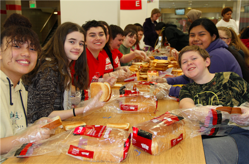 Ninth-grade students assemble sandwiches for homeless people in need.
