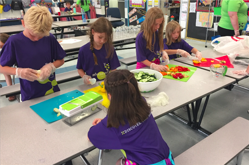 Adventures Plus students prepare vegetables for snack