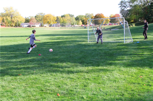 Coach prepares to block goal from soccer player