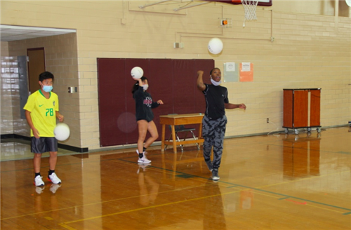 Students practice serving volleyball